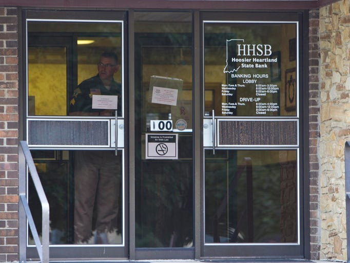A police officer looks out of the door of the Hoosier Heartland State Bank after it was robbed Friday, August 29, 2014, in Linden. Two men who robbed the bank in Montgomery County Friday are still at large.