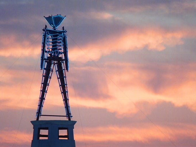 The sun rises behind a wood and neon statue, the centerpiece of the annual Burning Man festival north of Gerlach, Nev., on Monday, Aug. 26, 2002. The week-long festival in the Black Rock Desert started Monday.