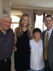 Harbaugh poses with his parents-in-law, Merle and Alta Feuerborn, and their granddaughter Kennedy Feuerborn.