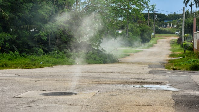 Smoke erupts from a manhole cover and other points in the neighborhood of Machanaonao, Yigo as Guam Waterworks Authority employees conduct a sewer smoke test on Friday, Oct. 27, 2017. The tests were conducted to check the integrity and safety of the underground sewer by locating breaks and defects in the system, said GWA employee Craig Paulino.