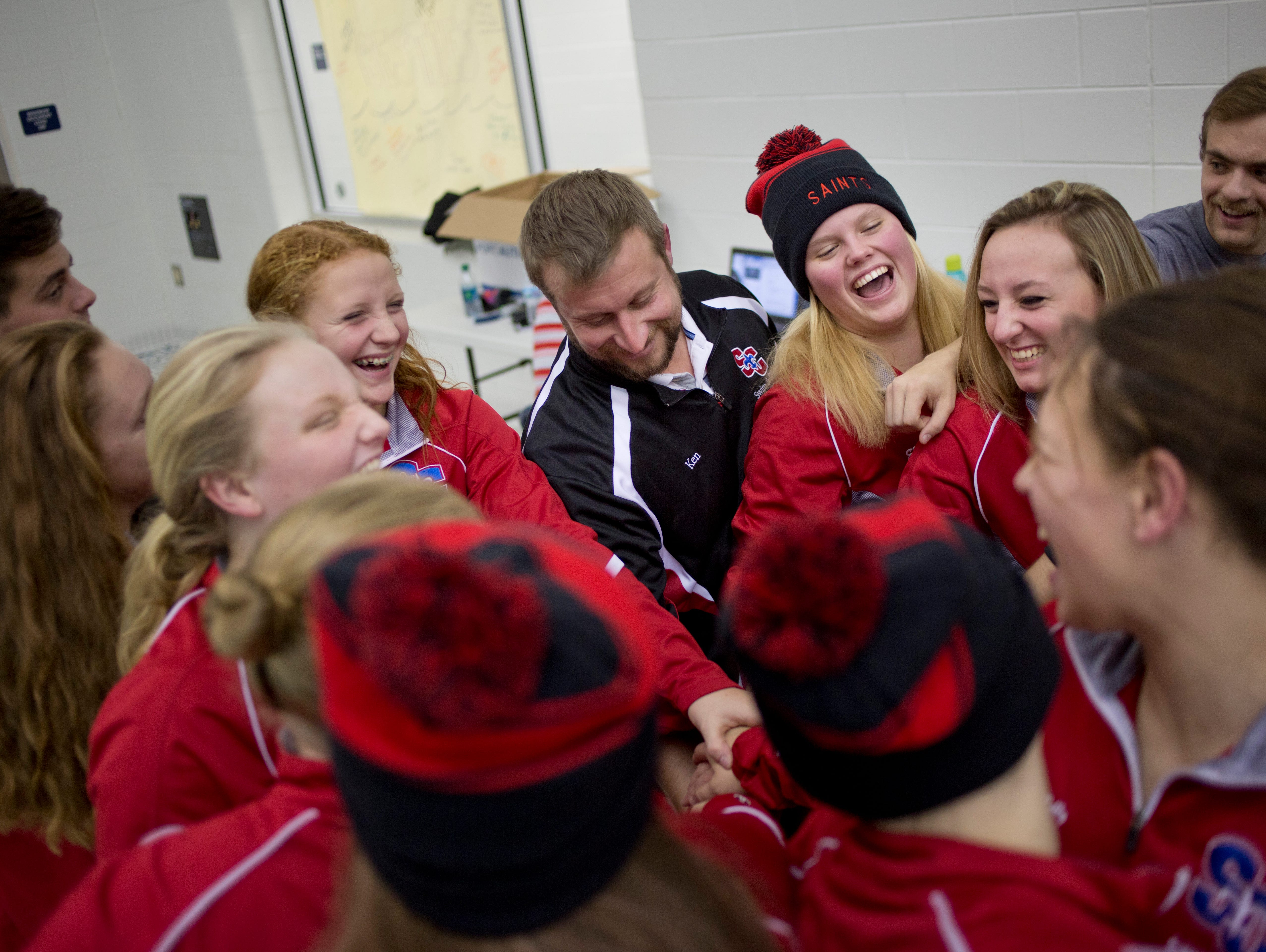 Players laugh as they put their hands in a huddle along with coach Ken Sygit during practice Wednesday, November 18, 2015 in Marysville.