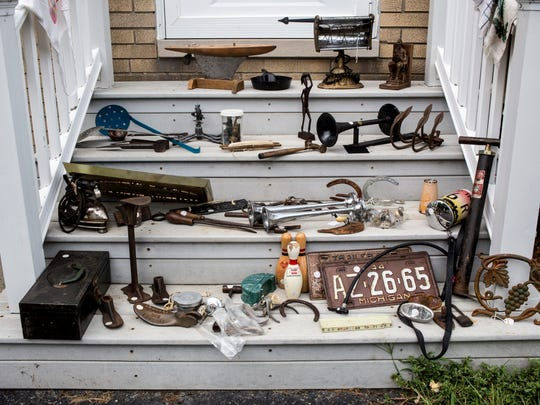 Dozens of antique items are neatly displayed on steps