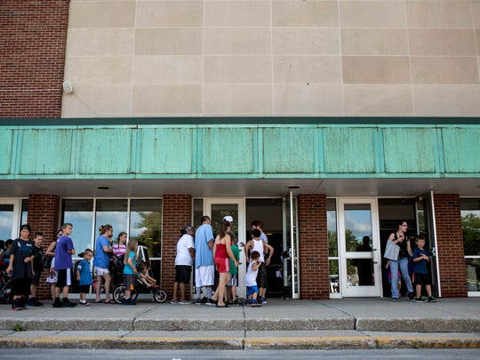 People line up outside during the annual backpack giveaway hosted by Blue Water Community Action Wednesday, August 17, 2016 at McMorran Arena in Port Huron.