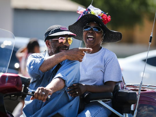 Parade participants point at friends during the Juneteenth parade Saturday, June 16, 2018, along Martin Luther King Drive.