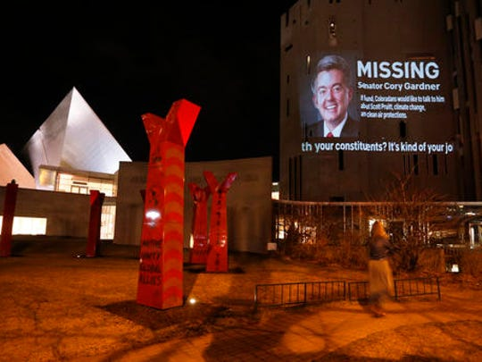 In this Feb. 21, 2017 photo, the face of Sen. Cory Gardner, R-Colo., accompanied by words and moving text, which is part of an environmental protest and unauthorized art installation, is displayed on the wall of the Denver Art Museum, in Denver.