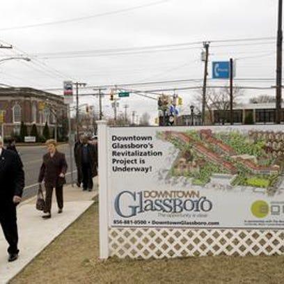 Glassboro Mayor Leo McCabe walks by sign promoting