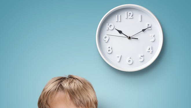 Young boy looking up at a clock.
