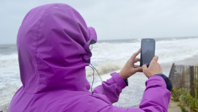 A woman takes photos of flooded Bethany Beach.
