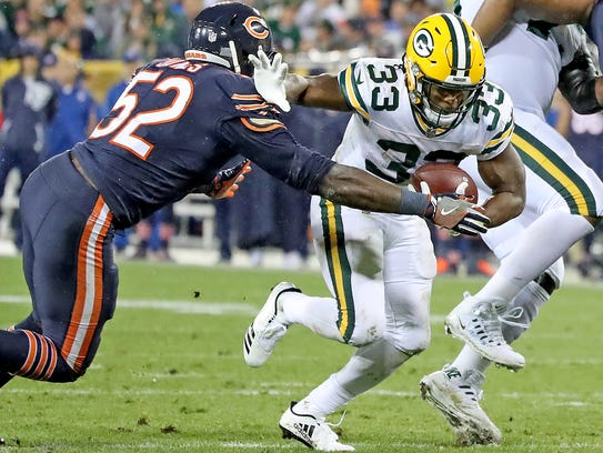 Green Bay Packers running back Aaron Jones pushes past