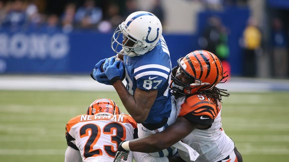 Colts receiver Reggie Wayne gets upended by Bengal players Terence Newman and Jayson DiManche after a reception in the fourth quarter. Indianapolis hosted Cincinnati at Lucas Oil Stadium Sunday, October 19, 2014.