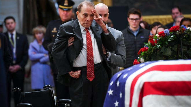 Former Sen. Bob Dole salutes the casket of former President George H.W. Bush on Dec. 4, 2018.