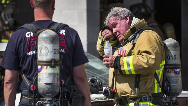 Chandler Fire Captain Kent Keller, right, wipes away sweat from his brow during a big box drill at the training academy in Chandler on June 21, 2017. Captain Allen Blaine is at left.