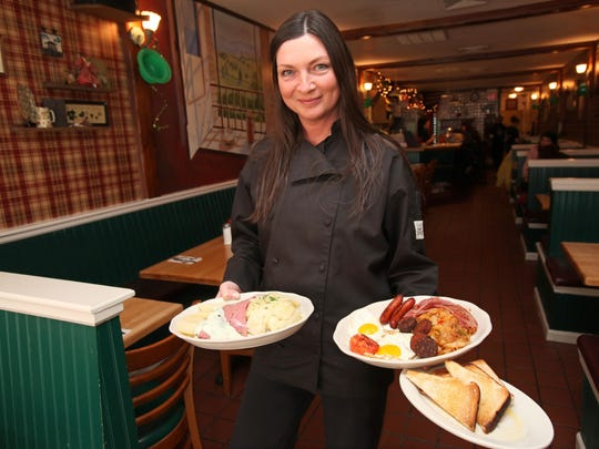 Eileen Collum of Eileen's Country Kitchen poses with a traditional Irish breakfast and corned beef and cabbage.