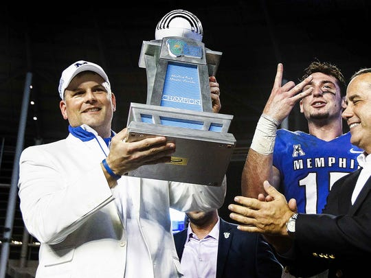 December 22, 2014 - Memphis head coach Justin Fuente (left) holds up the Miami Beach Bowl Championship trophy with game MVP quarterback Paxton Lynch (second Right) after defeating BYU 55-48 in Miami, Florida.  (Mark Weber/The Commercial Appeal)