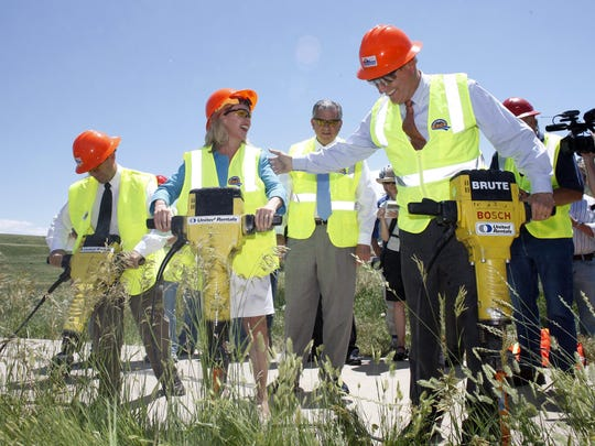 FILE - In this June 30, 2009 file photo, then-Transportation Secretary Ray LaHood, back, looks on as then-Colorado Gov. Bill Ritter, front right, Rep. Betsy Markey, D-Colo., center, and Rep. Ed Perlmutter, D-Colo., use jackhammers to break up a deteriorating bicycle path during a ceremony to break ground on the C-470 bike trail and highway reconstruction project in the west Denver suburb of Lakewood, Colo. President Donald Trump disparaged his predecessor's economic stimulus spending Tuesday as a windfall for social programs and said he's unaware of anything built from the money steered to infrastructure. (AP Photo/David Zalubowski, File)