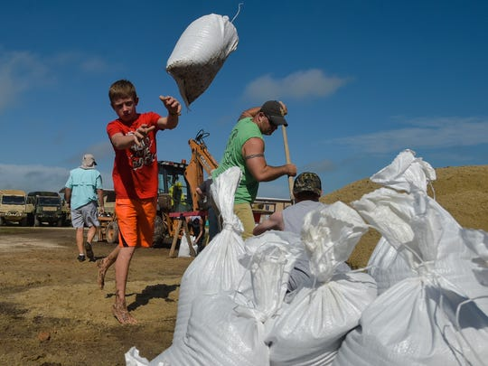 Dylan Heinan, among other volunteers, piles sandbags in an effort to stop flood waters from rising in Lake Arthur, La., Wednesday, Aug. 17, 2016.