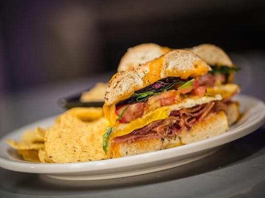 The Jungle's twist on a BLT is built with bacon, seasonal greens, tomato and a fried egg. A side of housemade hummus is at left.