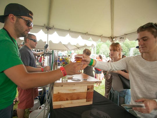 Chris Lee of Zero Gravity hands Citizen Zero beer to Keagan McDonnell of Proctor at the Vermont Brewers Festival on Saturday.