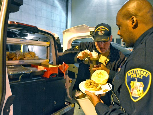 Never Forgotten BBQ owner Bill Kohler serves Baltimore City Police Officer Randolph a pulled pork sandwich Tuesday April 28, 2105 at the city police station.