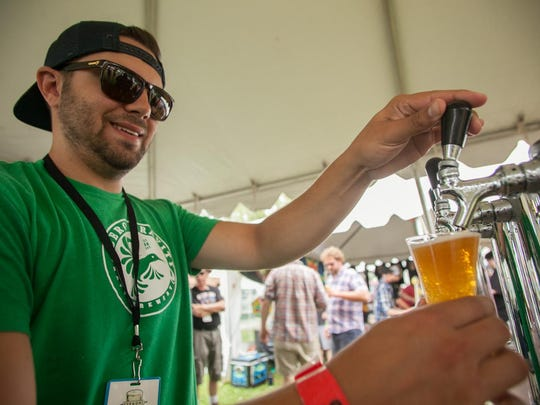 Chris Less of Zero Gravity Brewery pours a Citizen Zero beer at the 2015 Vermont Brewers Festival.