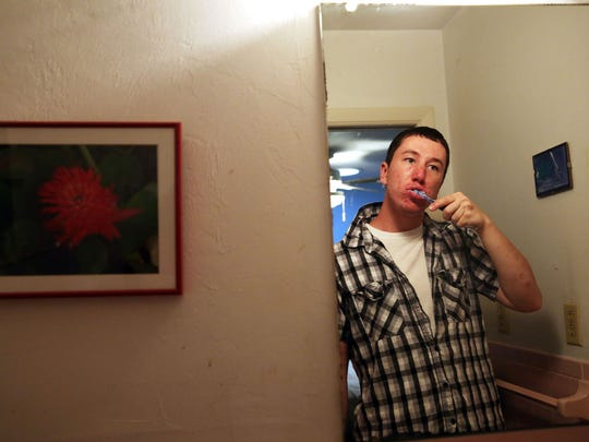 Walter Lasek Jr., 23, brushes his teeth after finishing dinner in his Naples Park home on Monday, April 18, 2016. Lasek lives at home with his mother Debby Kays and stepfather Terry. (Dorothy Edwards/Staff)