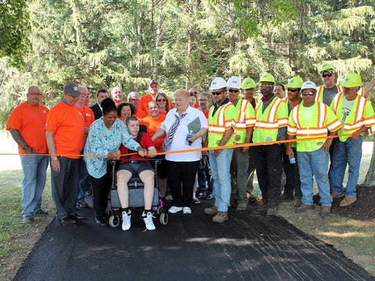 Matheny student Jacob Rolaf, assisted by personal care assistant Joan Marshall, left, and Tilcon's Chris Aaron, right, cuts the ribbon celebrating completion of the newly paved nature trail.