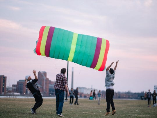 People try to help get a large parafoil kite in the