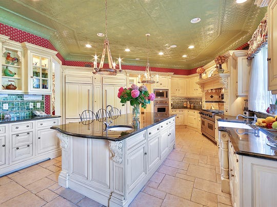 The kitchen is complete with custom Clive Christian cabinetry as well as limestone floors.