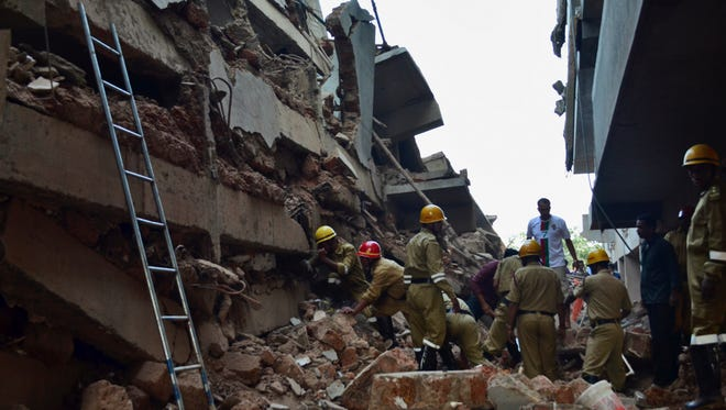 Rescue workers stand amid the debris of a building that collapsed in Canacona, India,  on Jan 4.
