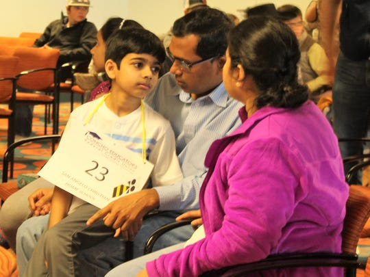 Akash Vukoti, a 3rd grader at San Angelo Christian Home School, meets with his parents in between rounds at the 30th annual San Angelo Spelling Bee