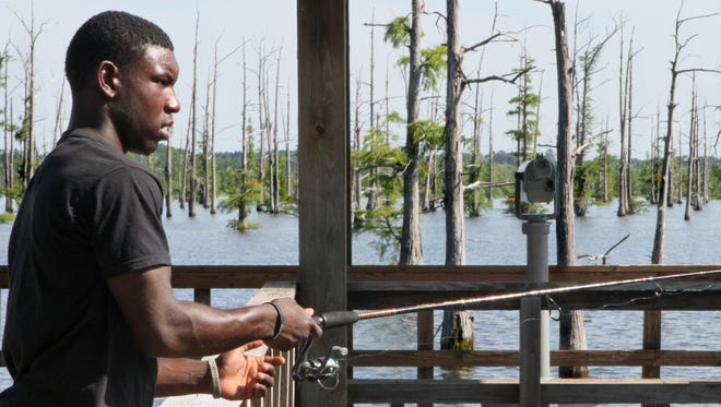 Monroe local Demone Jones patiently waits for a bass to tug his line as he fishes from the pier at Black Bayou Lake National Wildlife Refuge.