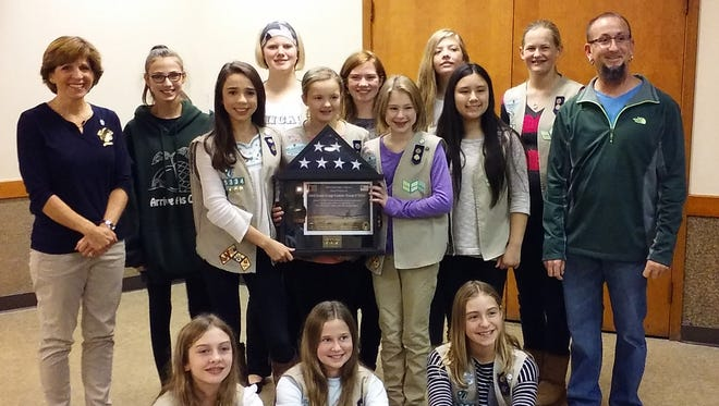 Brighton's Bill Tiemann, far right, personally delivered the flag to Girl Scout Troop No. 75334 in October.
