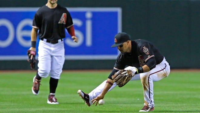 Diamondbacks third baseman Martin Prado (14) misses a pop fly by Philadelphia Phillies first baseman Ryan Howard (6) in the 8th inning of their MLB game Saturday, April 26, 2014, in Phoenix.