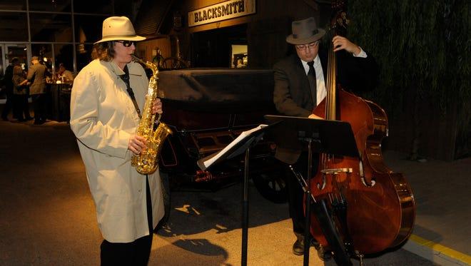 Jane K. Brown, left, goes incognito during Poppin' Pistons, the Reno Pops Orchestra fundraiser in 2013 at the National Automobile Museum. She and Josh Mittendorf entertained attendees.