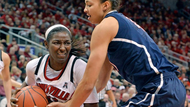 Louisville's Asia Taylor, left, battles Connecticut's Kiah Stokes for a loose ball during the second half of an NCAA college basketball game.