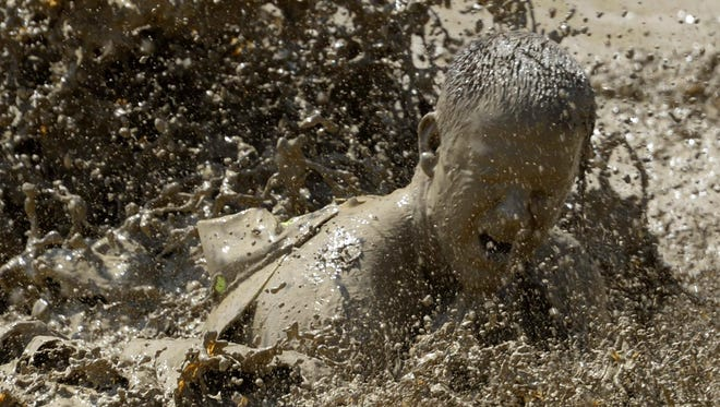 """A man hits the mud during the """"Tough Mudder"""" obstacle course event in San Bernardino, Calif. The event is part of a worldwide tour of extreme obstacle challenges before finishing with the annual """"World's Toughest Mudder"""" competition."""
