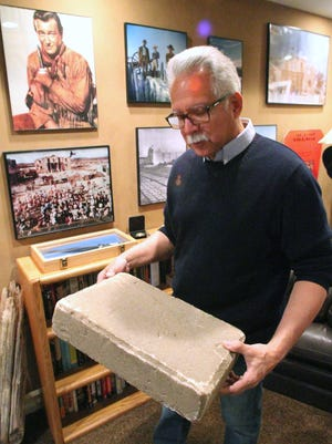 """John Wayne fan and author John Farkis shows a guest a Styrofoam block used during filming of explosions on the set of the John Wayne classic """"The Alamo."""" Farkis says that the faux blocks can be seen being tossed by special-effects pyrotechnics, simulating artillery hits on the structure of the Alamo."""