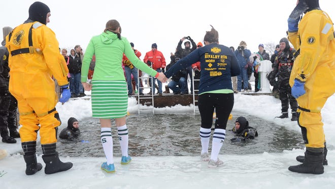 College rivals come together as Erica Somers, left, of Howell, and Lindsey Morse, of Marysville, hold hands as they make the icy leap together Sunday, Feb 22, during the Polar Plunge in St. Clair.