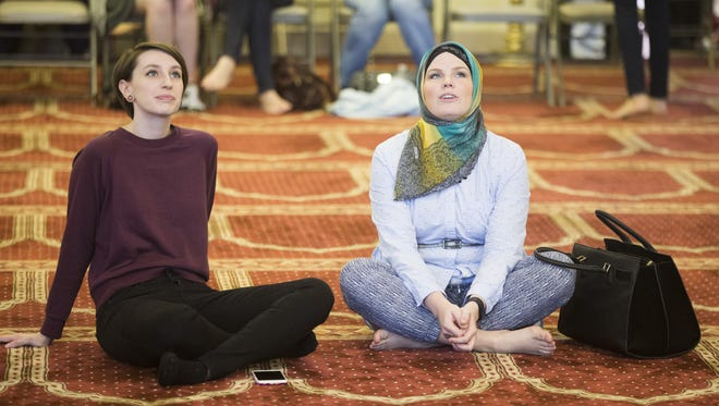 "Jessica Conditt (left) and Masha Priest sit and reflect as they enter a mosque for the first time during a rally of solidarity at the Islamic Community Center of Phoenix on Feb. 11, 2017, in Phoenix, Ariz. Conditt said that the rally was a ""really good reminder to love thy neighbor."""