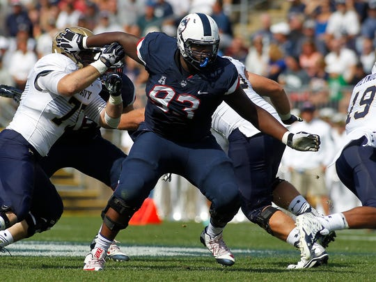 Connecticut defensive lineman Foley Fatukasi (93) during the second quarter of an NCAA college football game against Navy, Saturday, Sept. 26, 2015, in East Hartford, Conn. Three years after Superstorm Sandy forced his family from their home, Connecticut's Fatukasi has settled into a central part of the Huskies defensive line. (AP Photo/Stew Milne)