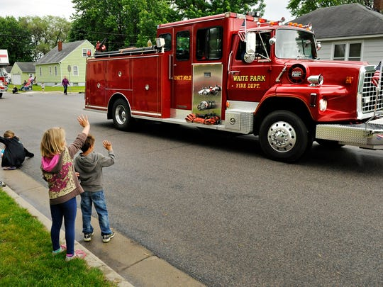 Children wave at the Waite Park Fire Department trucks as they hit their horns and sirens during the Waite Park Family Fun Fest parade in 2014.