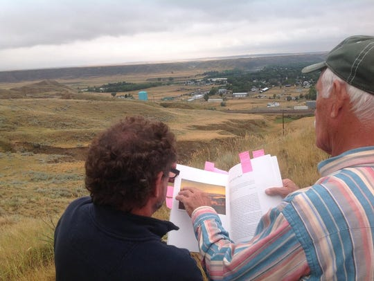 Jim Combs points out a landscape as seen in a Russell