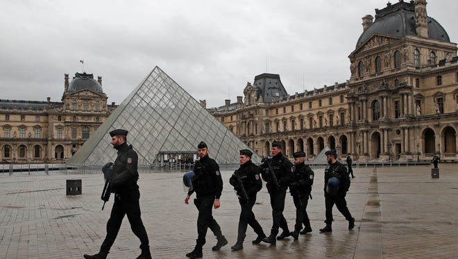 """Armed police officers patrol in the courtyard of the Louvre museum near where a soldier opened fire after he was attacked in Paris, Friday, Feb. 3, 2017. A knife-wielding man shouting """"Allahu akbar"""" attacked French soldiers on patrol near the Louvre Museum Friday in what officials described as a suspected terror attack. The soldiers first tried to fight off the attacker and then opened fire, shooting him five times."""