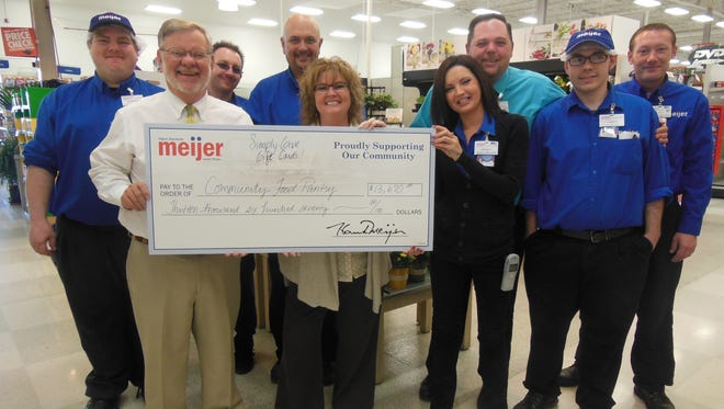 Community Food Pantry's Eldon Harzman, second from left, poses with a check from Meijer for the pantry.