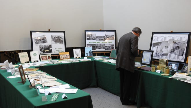 Charles Savage, associate professor of music at Ohio University's Zanesville Campus, looked through old photos at OUZ's 70 year celebration Saturday.