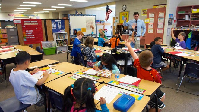 Third-graders interact with a teacher in a classroom.