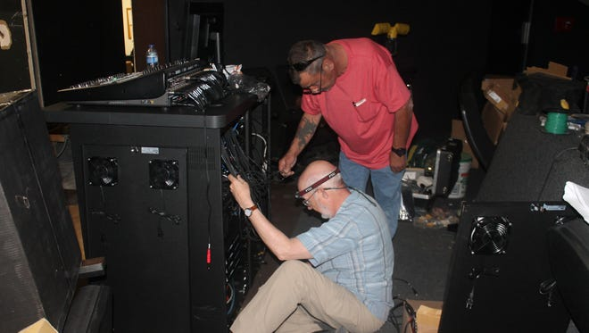 Field engineers Mike Sims , 58, top and Hue Sutherland began working on the laser system last Tuesday and will be done next Wednesday.  Before continuing, they both had to rearrange  a few wires so the sound system can be balanced.