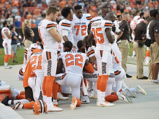 Members of the Cleveland Browns kneel during the national