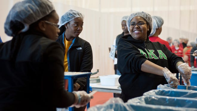 Asia Murphy, Austin Peay State University sophomore and Alpha Kappa Alpha sorority member, smiles as she scoops rice for food boxes during the university's Martin Luther King Jr. Day of Service event at the Foy Fitness and Recreation Center on Jan. 29, 2016. The event was sponsored by APSU Diversity Committee and Christian nonprofit Feed My Starving Children.