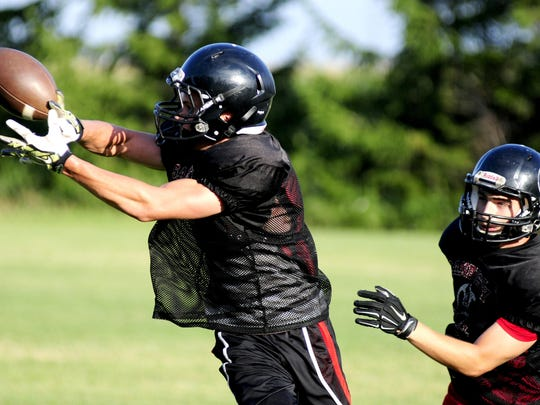 Casey Hyatt catches a pass in front of Wray Davault in a drill during a Sandusky football practice.